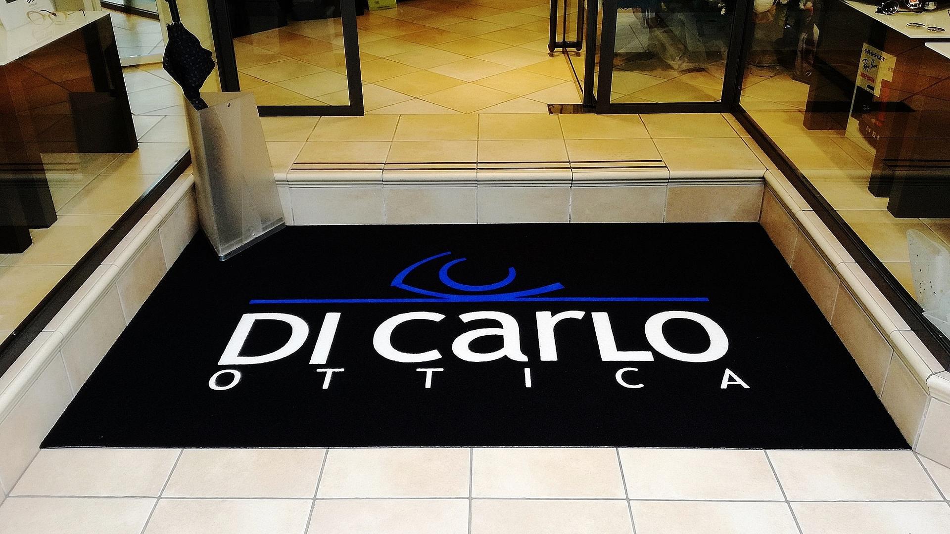 Ingresso di un negozio con un Tappeto intarsiato personalizzato con il logo Di Carlo Ottica di colore nero, blu e bianco