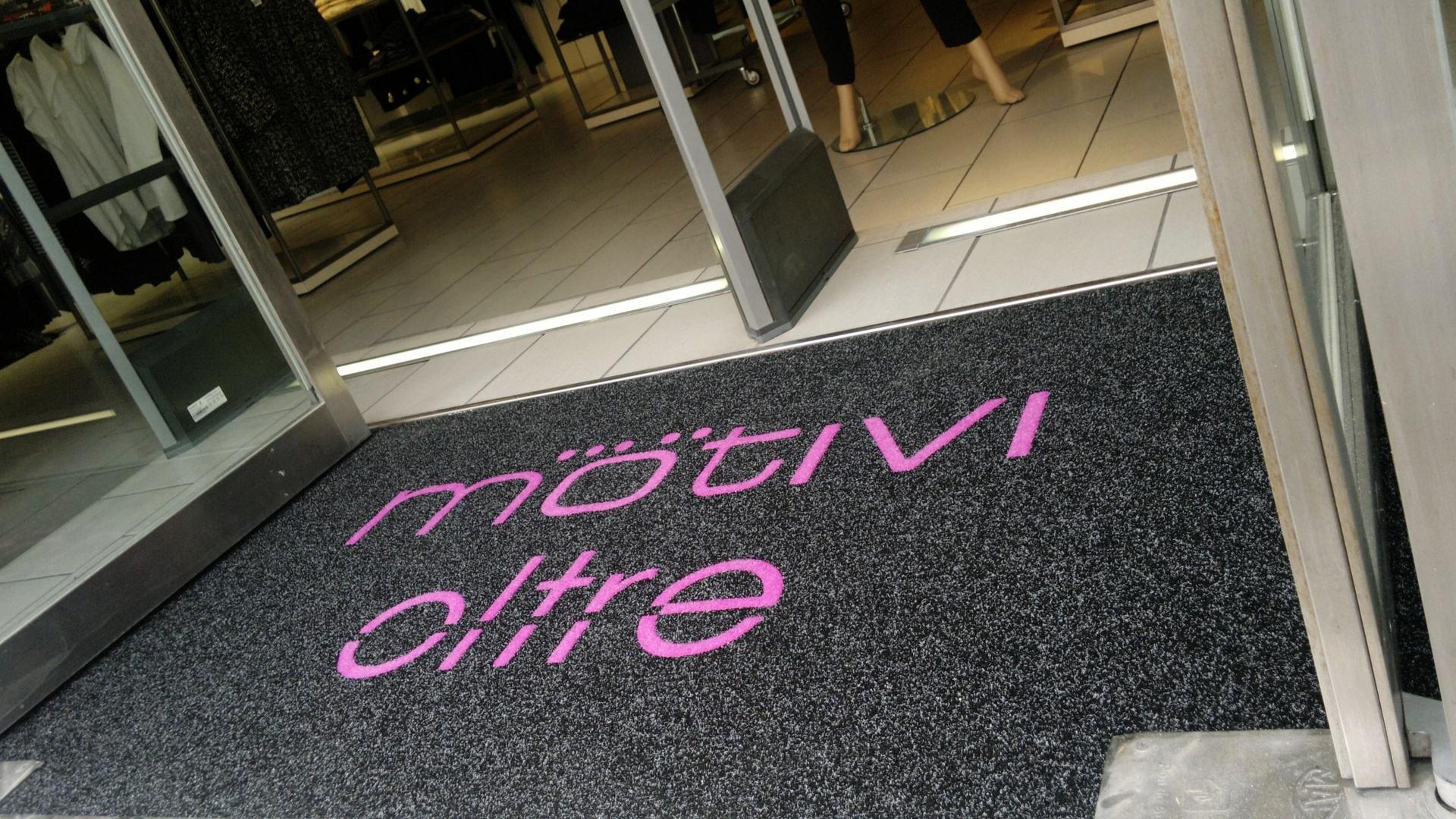 Ingresso di un negozio con un Tappeto intarsiato personalizzato con il logo Motivi e oltre di colore nero puntinato e fuxia